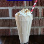 sonic coconut cream pie shake in a clear glass with a pink and white striped straw against a brick background