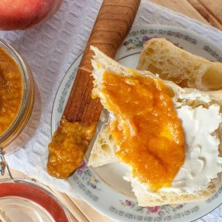 Crock Pot Peach Butter Recipe perfect for canning or enjoying fresh! This slow cooker recipe is so easy and you can easily make it a spiced peach if you want! Use your canning jars to make this into a great gift idea! This fresh peach recipe is beyond delicious and easy to make!