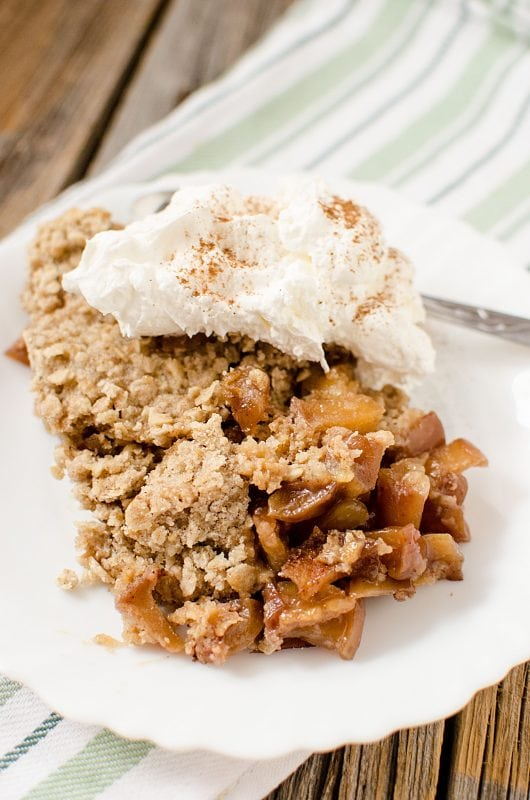 Easy crock pot slow cooker caramel apple crisp that is perfect for family dessert! A great fall comfort food!