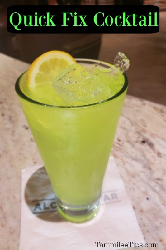 bright green cocktail in a tall glass with a white napkin