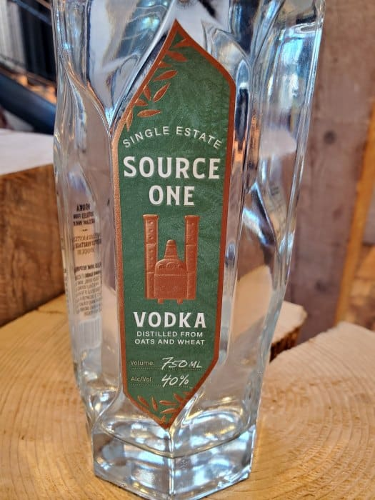 Close up of Bentley Heritage Source One Vodka bottle on a wood platform