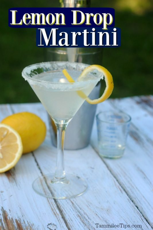 Lemon Drop Martini in a clear glass martini glass with a lemon twist and sugared rim. Cocktail shaker and a couple of lemons behind the cocktail with a white and green background.